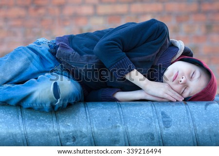 young homeless boy sleeping on a heating pipe, city, street