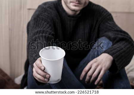 Young homeless man sitting on the ground and asks for help - stock photo