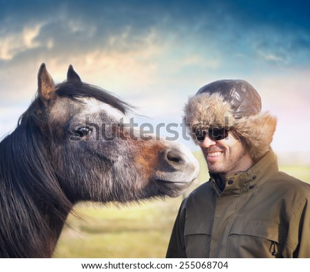 Young horse looking at smiling man in hat ear flaps  - stock photo