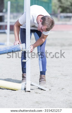 young horse rider placing jumping poles on a horse jumping session - focus on the face