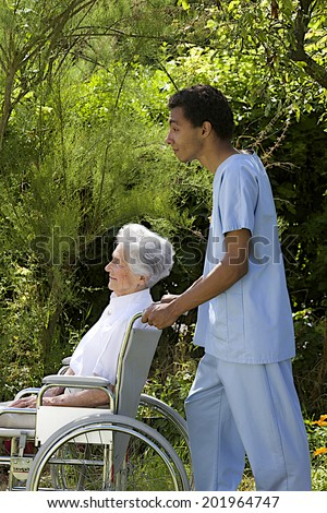 Young hospital staff pushing  happy senior patient in wheelchair outdoors