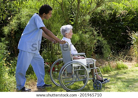 Young hospital staff pushing  happy senior patient in wheelchair outdoors  - stock photo