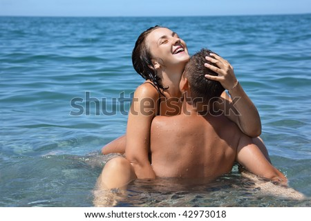 young hot woman sitting astride man in sea near coast, closed eyes