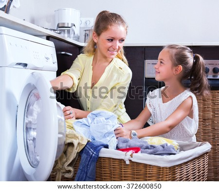 Young housewife and little girl doing laundry together - stock photo