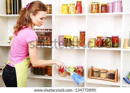 Young housewife cleaning up kitchen on grey background - stock photo