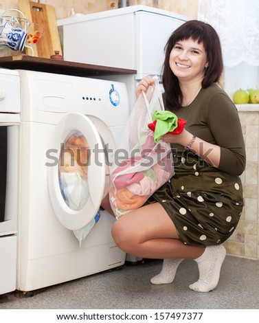 Young housewife doing laundry at her home