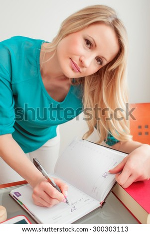 young housewife drinking coffee and reviewing accounts