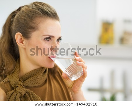 Young housewife drinking water in kitchen - stock photo