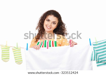 Young housewife hanging clothes on the line, isolated on white background - stock photo