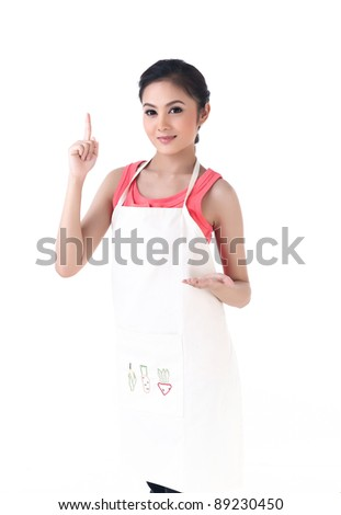 Young housewife holding your product and other hand point to your text - stock photo