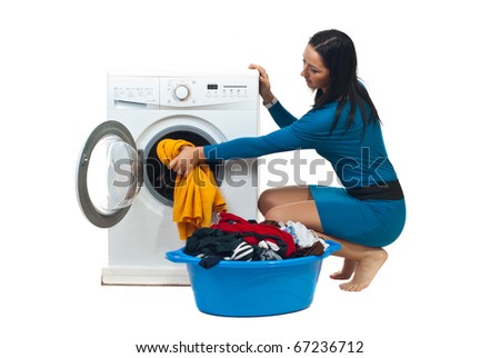 Young housewife in blue dress loading washing machine isolated on white background - stock photo