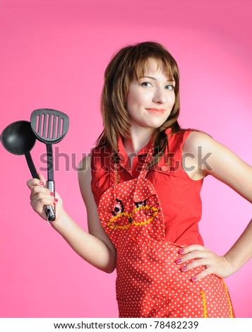 Young housewife in red apron with ladle