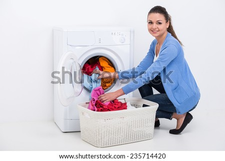 Young housewife is doing laundry with washing machine at home. - stock photo