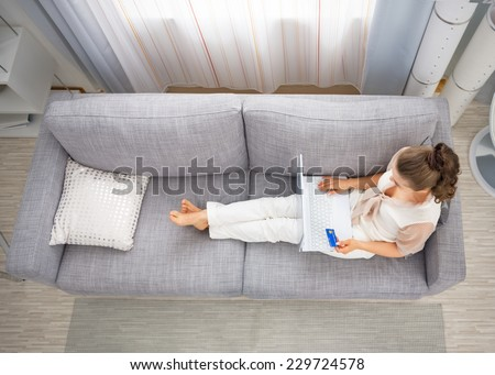 Young housewife laying on sofa in living room and making online shopping - stock photo