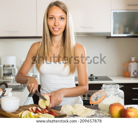 Young housewife preparing apple cake in kitchen - stock photo