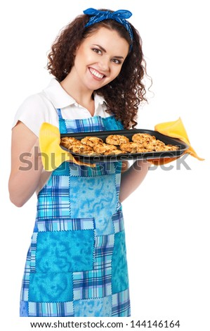Young housewife showing tray of cookies fresh from oven, isolated on white background