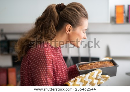 Young housewife smelling baking dish with bread - stock photo