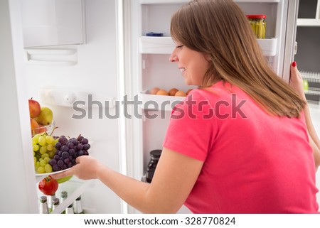Young housewife take fresh sweet grapes from refrigerator - stock photo