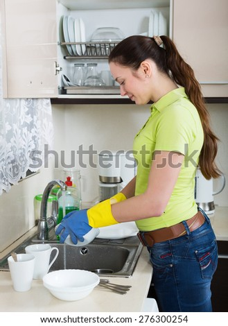 Young housewife washing dishes in the kitchen
