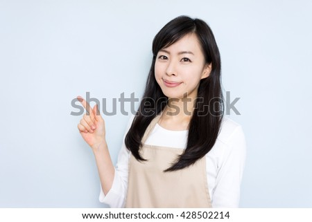 young housewife with apron showing copy space against blue background - stock photo