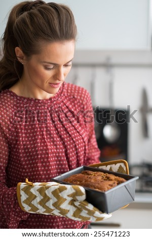 Young housewife with baking dish with bread