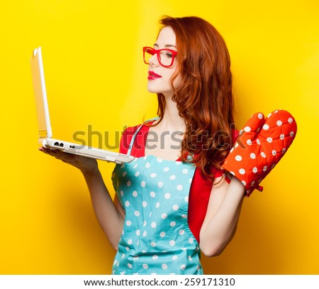 Young housewife with computer and oven gloves on yellow background - stock photo
