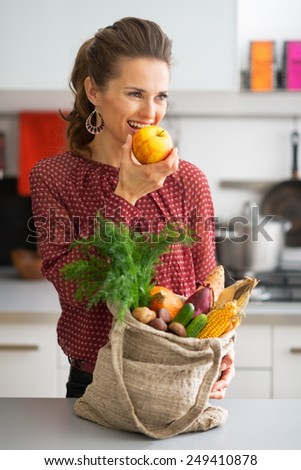 Young housewife with purchases from local market eating apple - stock photo