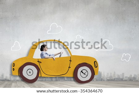 Young humorous woman driving drawn funny car - stock photo