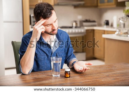 Young hungover man taking some pills to cure a headache at home - stock photo