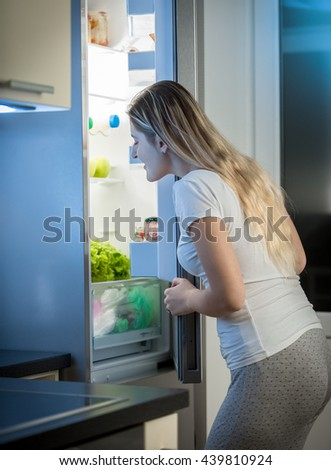 Young hungry woman looking inside open fridge at late night