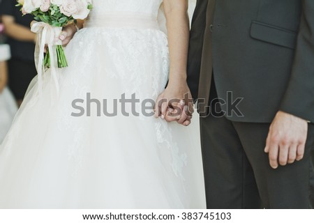 Young husband and wife holding hands.