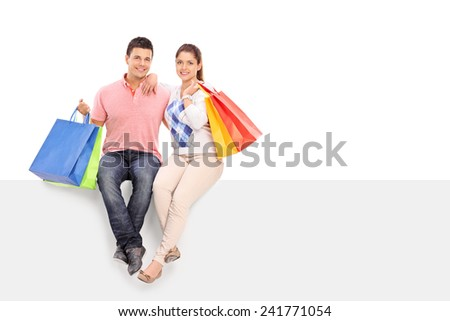 Young husband and wife holding shopping bags seated on a blank panel isolated on white background - stock photo