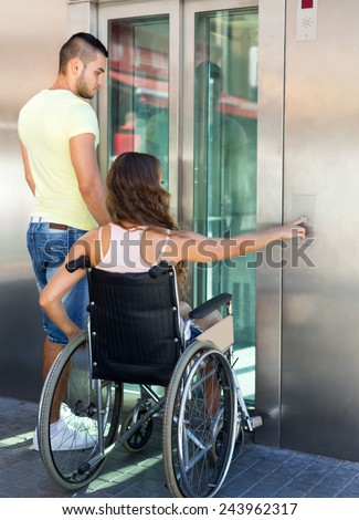 Young husband and wife on wheelchair getting out from passenger lift