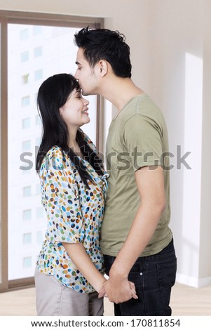 Young husband kissing his wife in a new home