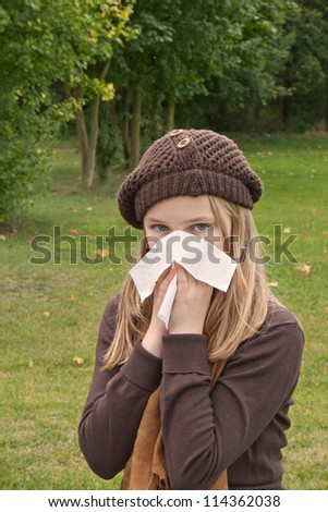 young ill girl with scarf, hat and handkerchief/snuffle/ill