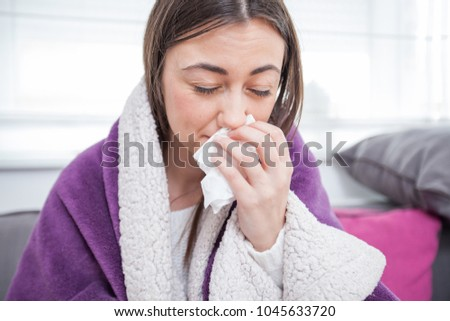 Young ill woman, blowing nose, covered with blanket,at home