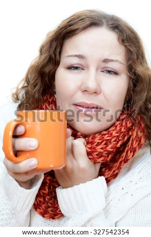 Young illness woman drinking tea with wrapping scarf on neck - stock photo