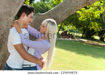 Young in love couple embracing under tree. - stock photo
