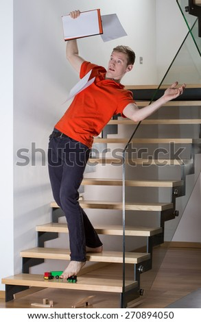 Young inattentive man slipping on stairs on a toy - stock photo