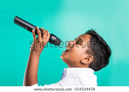 young indian boy in white shirt yelling in microphone, little kid singing, Little indian boy with microphone sings a song, Singing asian Young boy, Cute young asian boy singing into a microphone - stock photo