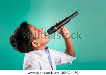 young indian boy in white shirt yelling in microphone, little kid singing, Little indian boy with microphone sings a song, Singing asian Young boy, Cute young asian boy singing into a microphone