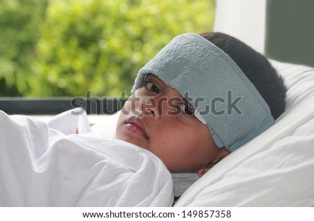 Young indian boy ( kid ) suffering high fever ( flu ) & getting treatment. A wet cloth is kept on forehead to reduce the temperature - stock photo