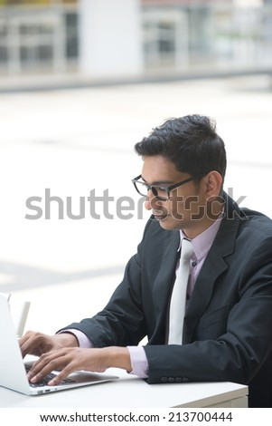young indian business male on laptop and coffee at a cafe - stock photo