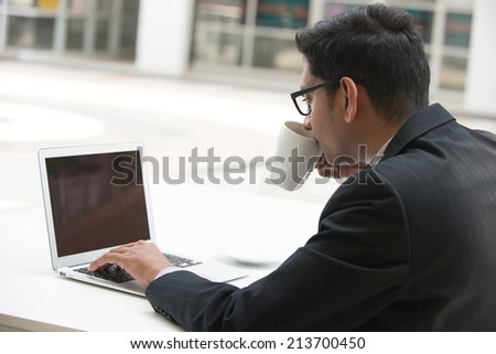 young indian business male on laptop and coffee at a cafe, focus on computer - stock photo