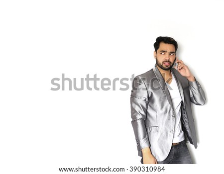 Young Indian business man holding mobile phone, using smartphone, making a call, talking on the phone, against a white background