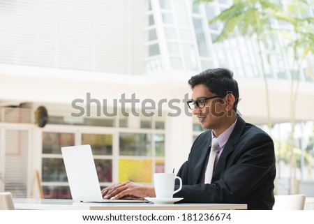 young indian business man on laptop and coffee - stock photo