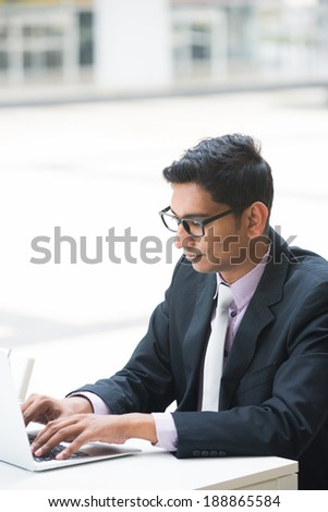 young indian business man on laptop and coffee at a cafe, focus on computer  - stock photo