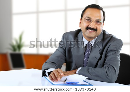 Young Indian business man sitting at his desk - stock photo