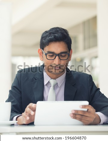 young indian business man with a tablet computer and coffee at a cafe - stock photo