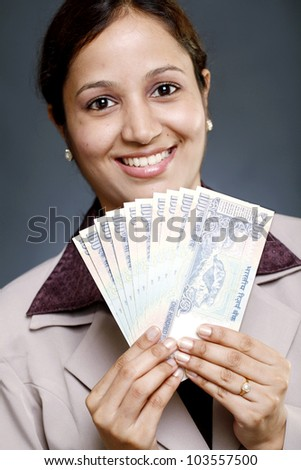 Young Indian business woman holding currency notes - stock photo